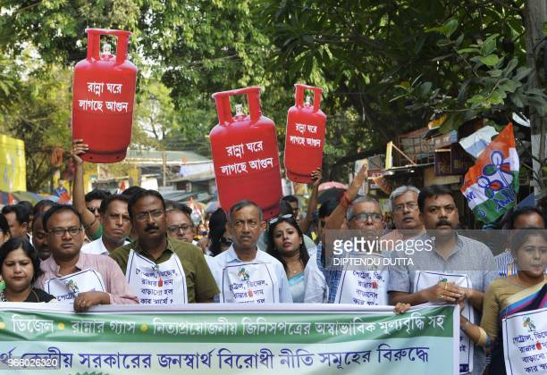 Indian supporters of Trinamool Congress party hold cutout replicas of LPG cylinder during a protest against the Bharatiya Janata Party lead central...