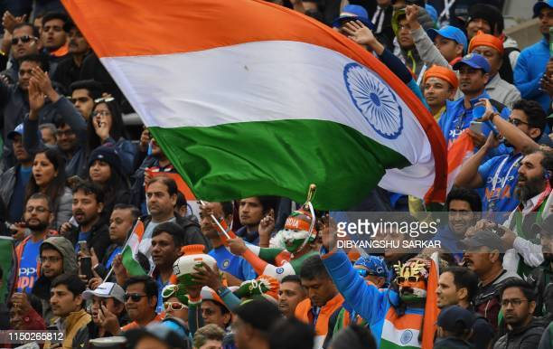 Indian supporters wave a national flag as they celebrate after victory in the 2019 Cricket World Cup group stage match between India and Pakistan at...