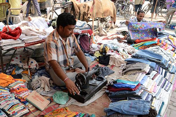 Indian tailor Pappi repairs used clothes at roadside stalls in Amritsar on May 17 2015 The tailor repairs used clothes to earn around 300 Indian...