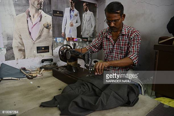 Indian tailor Ram Bachchan uses a sewing machine to stitch trousers at his shop in Amritsar on September 24 2016 Bachchan earns between 10001500 INR...