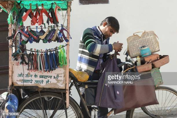 Indian tailor with a mobile shop on his bicycle repairs a jacket in Amritsar on February 6 2018 / AFP PHOTO / NARINDER NANU