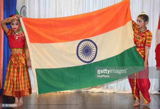 Indian Tamil girls representing the state of Tamil Nadu hold the Indian flag while competing in a traditional Indian folk dance competition held in...