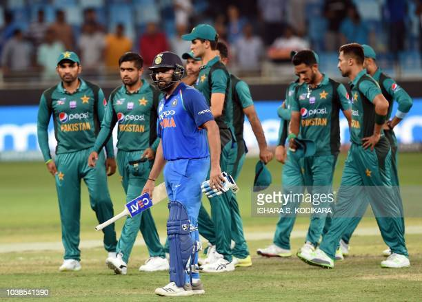 Indian team captain Rohit Sharma and Pakistan team leave the field after India won by 9 wickets during the one day international Asia Cup cricket...