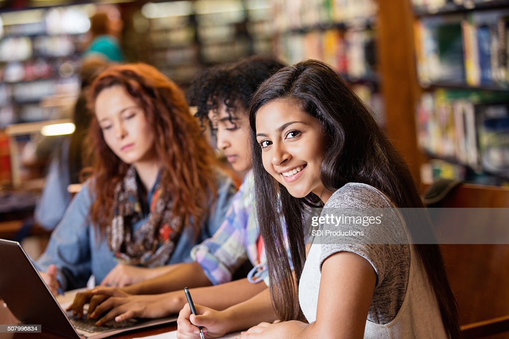 Indian teen studying in library with college age friends : Stock Photo