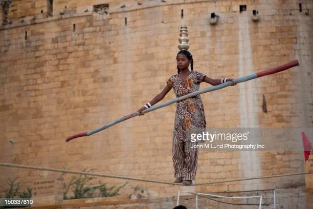 Indian teenaged performer walking on tightrope,Jaislamer, India