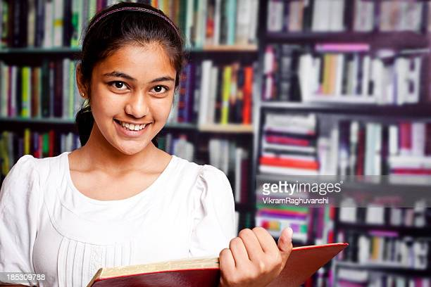 Indian Teenager Girl studying in a Library with Bookshelf