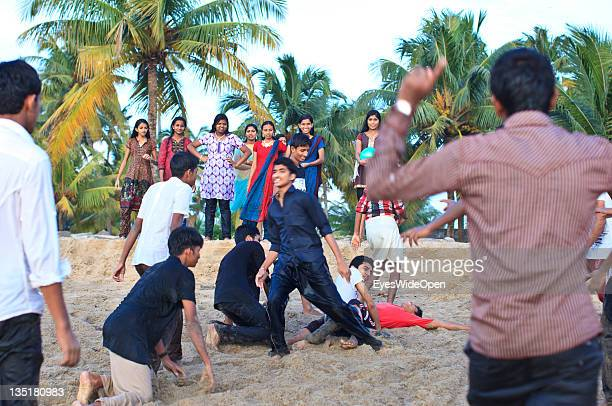 Indian teenagers boys and girls playing at Cherai Beach Vypeen Island in the Cochin area on November 23 2011 in Cochin Kerala India