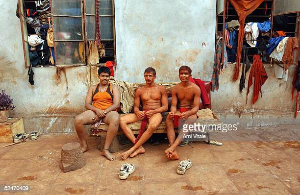 Indian teenagers rest outside their living quarters after practice of the three thousand year old sport known as 'Kushti' a form of wrestling in its...