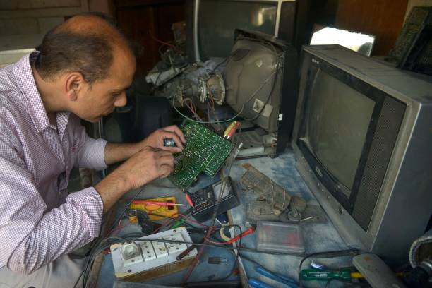 Indian television repairman Balwinder Pal works at his shop in Amritsar on May 26 2017 Pal said he earns around 300600 INR a day for his electronics..