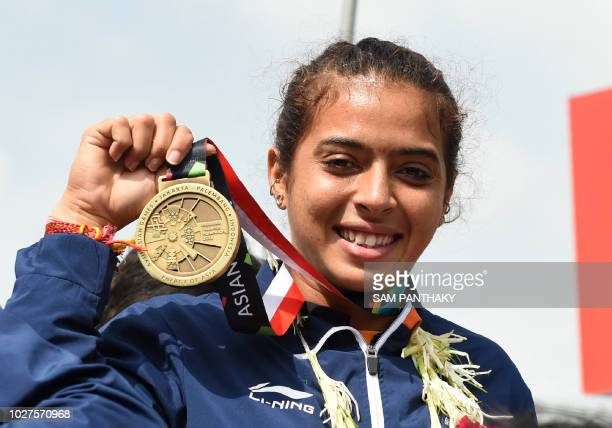 Indian tennis player Ankita Raina poses as she holds her medal during her arrival at the Sardar Vallabhbhai Patel International Airport in Ahmedabad...