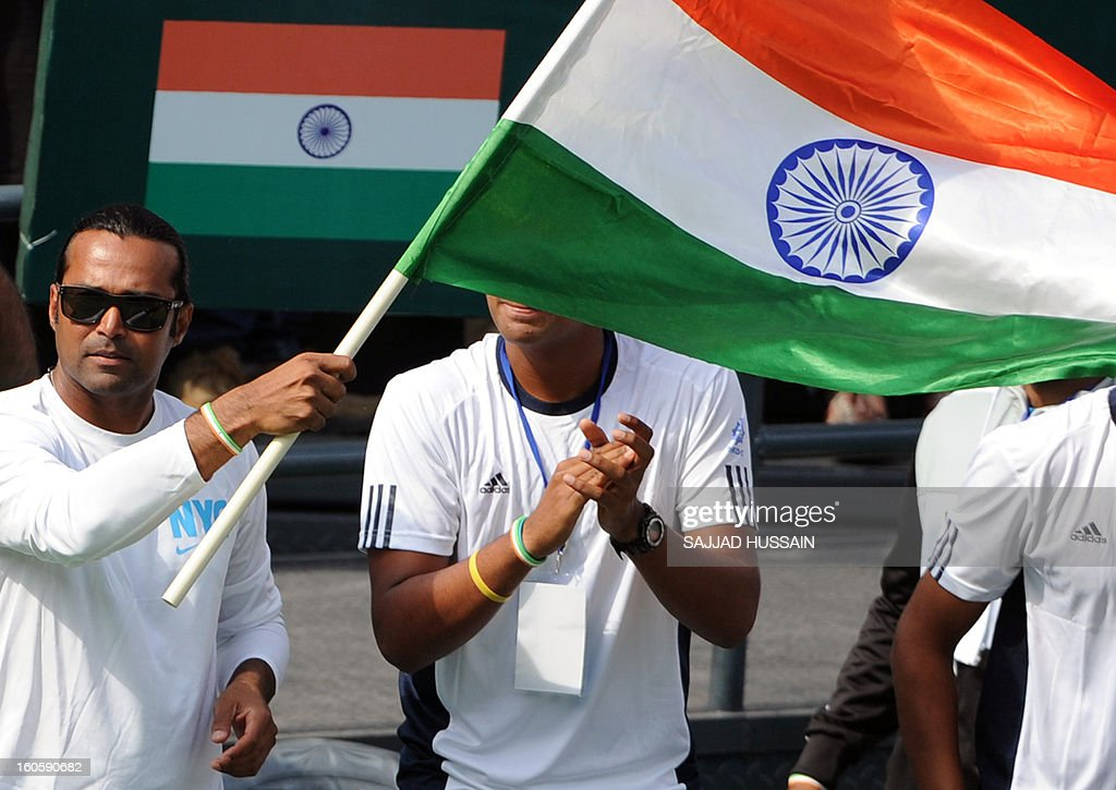 Indian tennis player Leander Paes (L) waves his national flag as he encourages compatriot Virali-Murugesan Ranjeet in his match against South Korean opponent Jeong Suk-Young during the reverse singles Davis Cup match at the Delhi Lawn Tennis Association (DLTA) courts in New Delhi on February 3, 2013. South Korea took both the reverse singles to complete a 4-1 victory over depleted India in the Asia-Oceania group one first round Davis Cup tie in New Delhi.