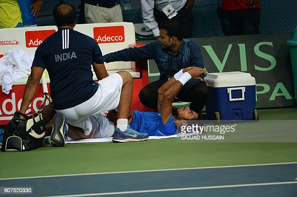 Indian tennis player Sumit Nagal receives medical treatment on court during his Davis Cup singles match against Spain's Marc Lopez in New Delhi on...