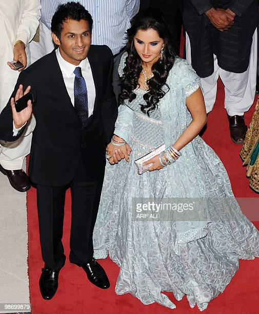 Indian tennis star Sania Mirza holds her husband and Pakistani cricketer Shoaib Malik's hand as they arrive at their wedding reception in Lahore on...