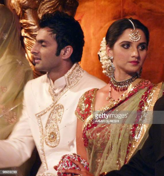 Indian tennis star Sania Mirza sits with her husband and Pakistani cricketer Shoaib Malik during their wedding reception in Sialkot on April 25 2010...