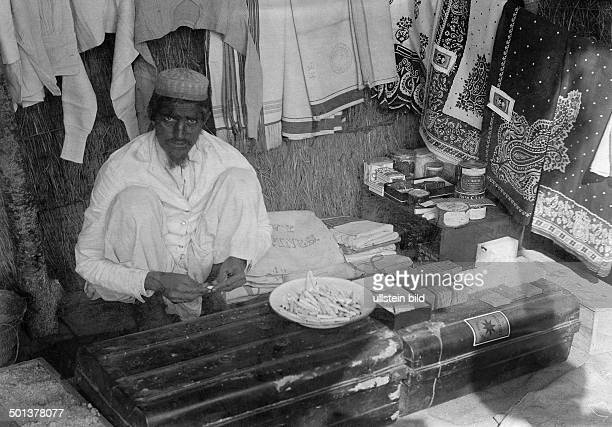 Indian textile dealer in his shop on the street probably Tanzania undated probably in the 1910's