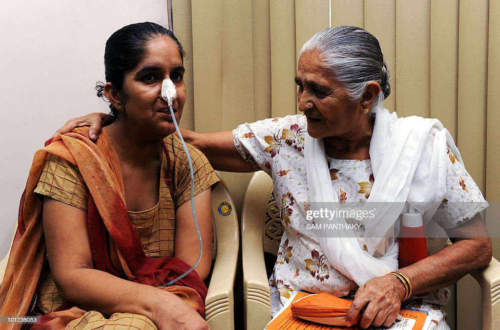 Indian tobacco consumer and cancer patient Seemaben (L) is comforted by her mother-in-law Meeraben during a media briefing on cancer at the Gujarat Cancer and Research Institute in Ahmedabad on May 28, 2010. Different types of cancer is on the rise in women in India and in most cases owing to chewing tobacco. World No Tobacco Day is observed on May 31, 2010. AFP PHOTO/ Sam PANTHAKY