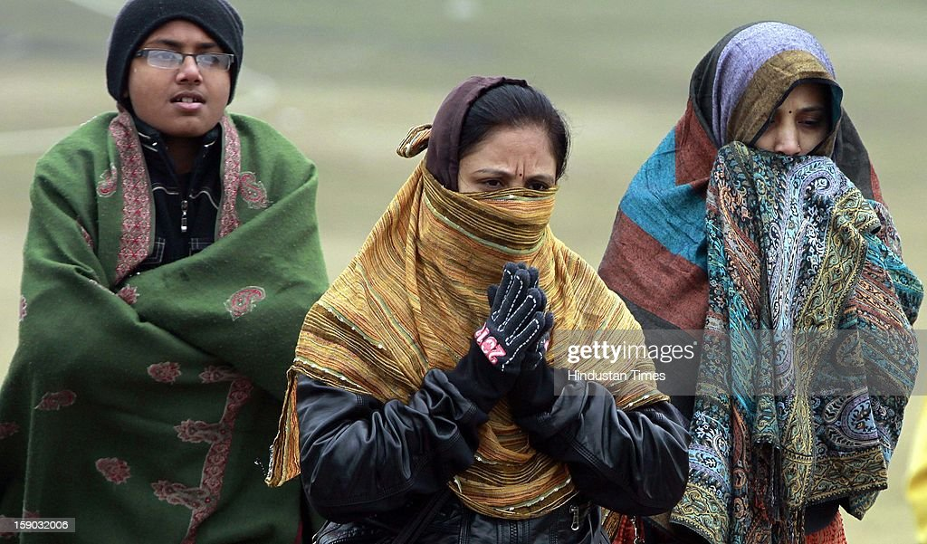 Indian Tourist cover themselves with woolens at Rajghat on January 6, 2013 in New Delhi, India. Setting a new low for temperature this winter, mercury in the national capital on Sunday fell to 1.9 degrees Celsius - five notches below average. This is the lowest recorded in Delhi in five years.