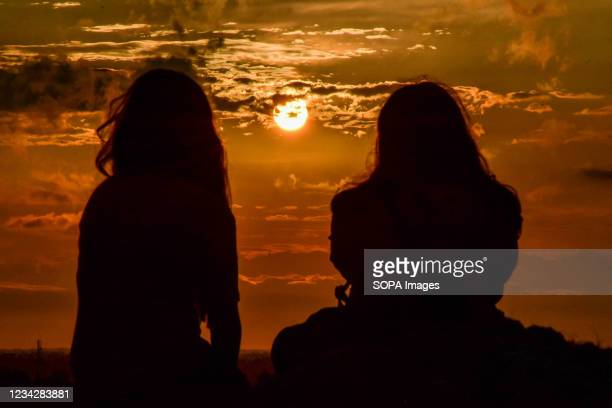 Indian tourists enjoy the view of the sunset on top of a hill in Manasbal, about 30kms from Srinagar. The India Meteorological Department issued a...