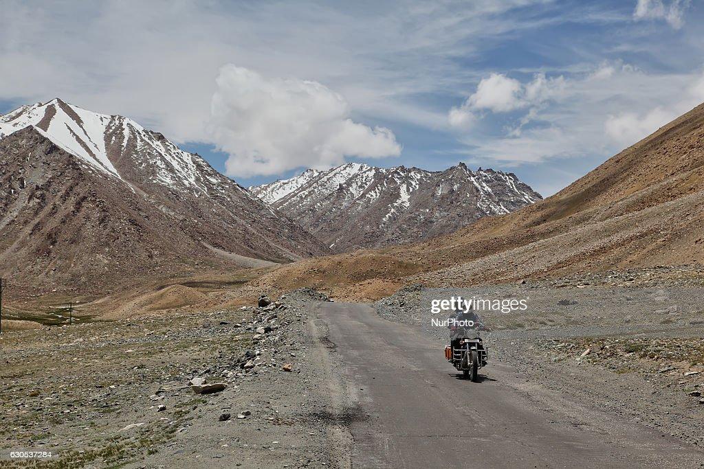 Indian tourists riding a Royal Enfield motorbike along a road cutting through the Himalayas in Tsoltak Ladakh Jammu and Kashmir India
