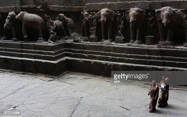 Indian tourists walk past a large Hindu stone structure at The Ellora Caves in the western Indian state of Maharashtra on November 16 2012 The 34...