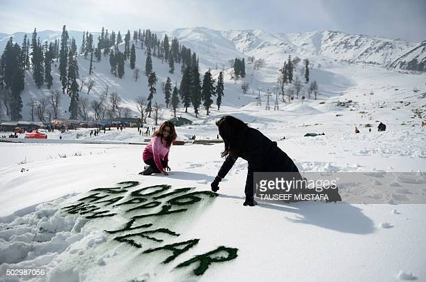 Indian tourists write in the snow as they celebrate the New Year in Gulmarg about 55 kms north of Srinagar on December 31 2015 Gulmarg is the main...