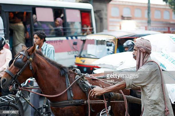 Indian trader with sacks of rice on horse and cart