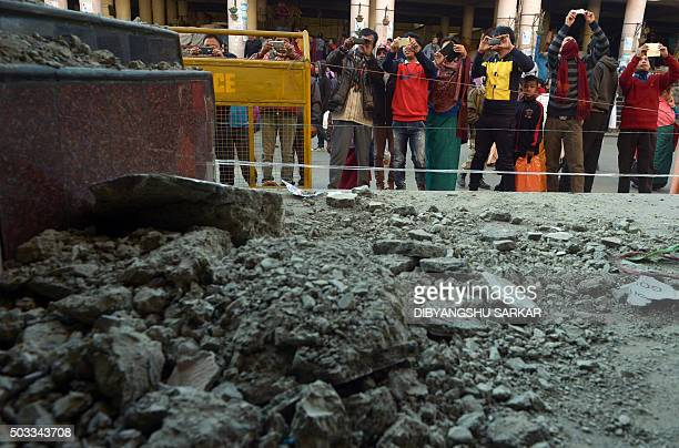 Indian traders and onlookers take pictures of a damaged market building after a 67 magnitude earthquake in Imphal on January 4 2016 At least nine...