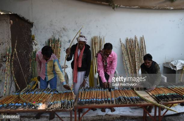 Indian traders from Chota Udepur a tribal dominated region of Gujarat arrange bows and arrows for sale outside the venue of a mass wedding for...