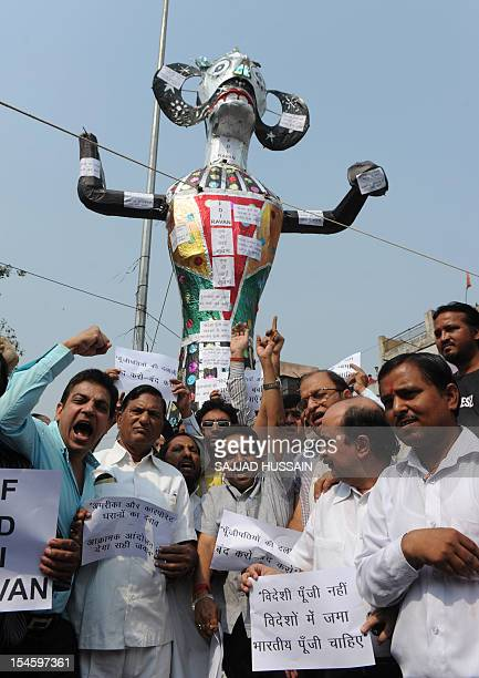 Indian traders shout slogans in front of an effigy representing a Foreign Direct Investment Ravana in New Delhi on October 23 2012 The rally was...
