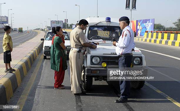 Indian traffic policemen writes a traffic ticket for a car that drove on a lane exclusively catering to athletes and the delegations during the...