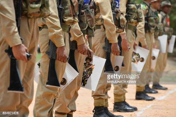 Indian trainee recruits hold onto target boards after a shooting practice session at the firing range of the Parachute Regiment Training Centre in...