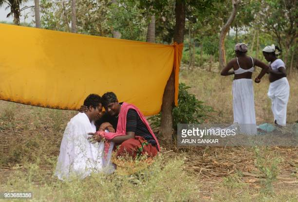 Indian transgender devotees embrace as others dress up in a white sari after a ritual signifying their marriage to the Hindu warrior god Aravan at...