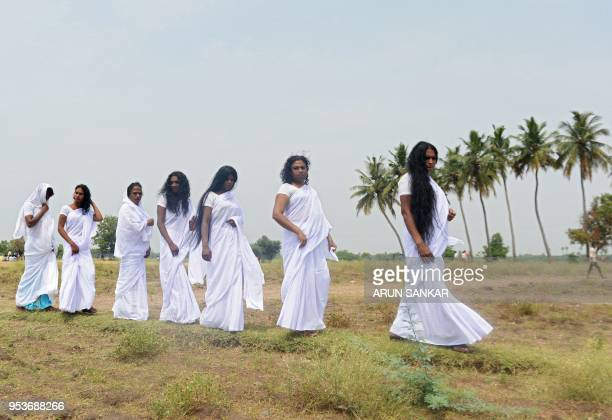 Indian transgender devotees wearing white saris walk on a field after a ritual signifying their marriage to the Hindu warrior god Aravan at the...