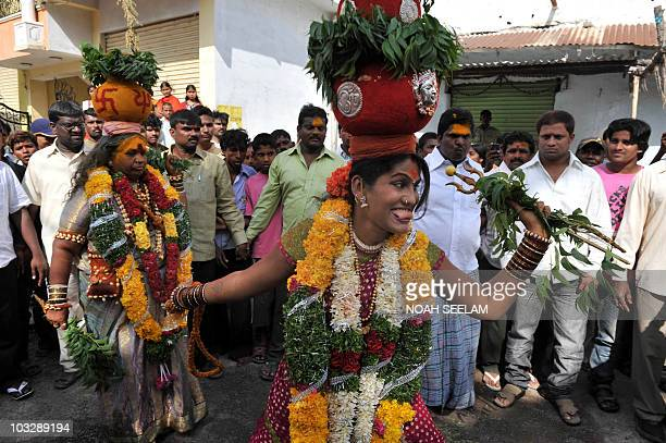 Indian transgender Kolipaka Shyamala Devi carries a 'ghatam' pot filled with cooked rice and decorated with neem leaves while dancing in a trance...