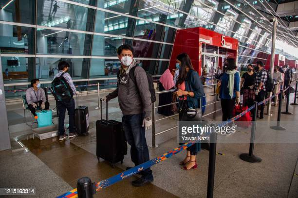 Indian travelers waits in queue to disinfect their luggage at the dropoff point before entering Terminal 3 of the Indira Gandhi International Airport...