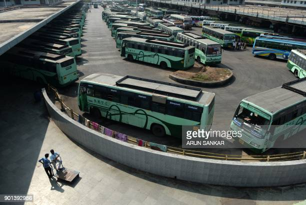 Indian travellers stand next to buses parked at a depot during a transport strike in Chennai on January 5 2018 The Tamil Nadu State Transport...