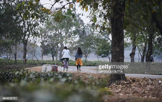 Indian tribal residents travel along a road at the Dagapur tea garden on the outskirts of Siliguri in the eastern state of West Bengal on January 23...