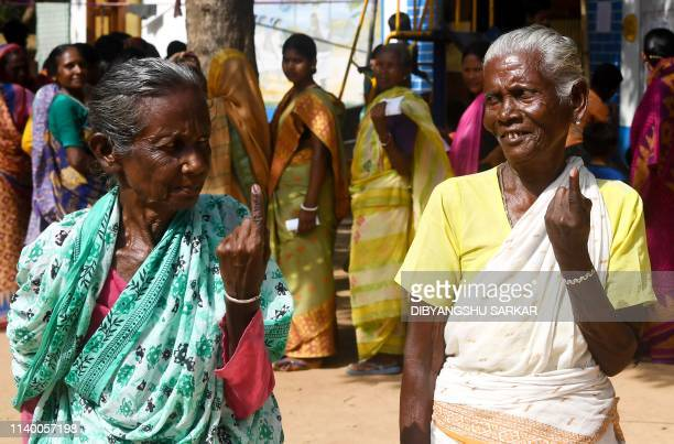 TOPSHOT Indian tribal voters pose for photographs showing their inked finger after casting their vote at a polling station in Illambazar area of the...