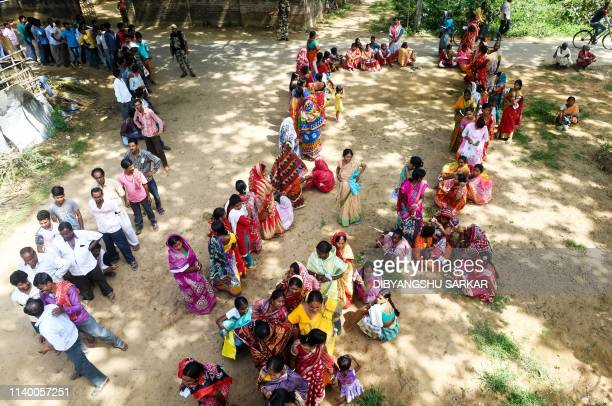 Indian tribal voters stand in a queue to cast their vote at a polling station during the fourth phase of general election in Illambazar area of the...
