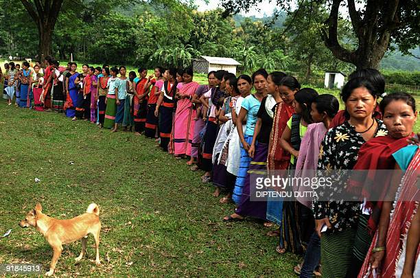 Indian tribeswomen queue to cast their votes at a polling station in the village of Kokila village some 45 kms from Itanagar on October 13 for state...