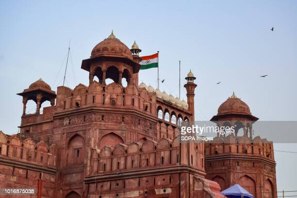 Indian Tricolour flag waves high above within the intricate architectural details of the Red fort in Delhi Built from red sandstone in1639 the Red...