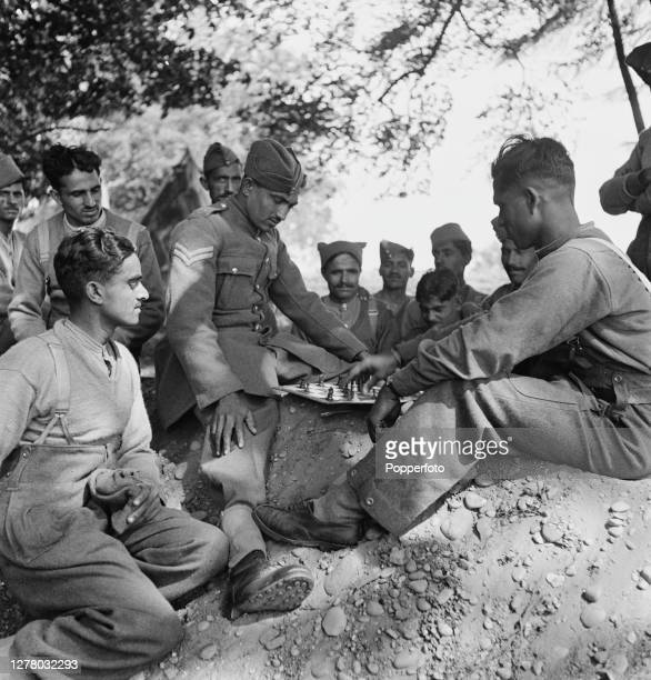 Indian troops from a unit of the British Indian Army play a game of chess on a board at their camp in the English midlands during World War II on...