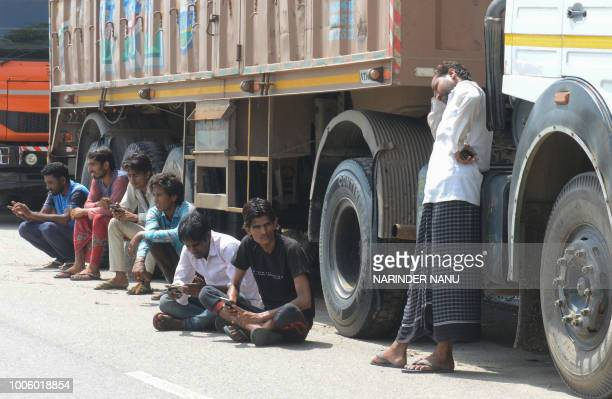Indian truck drivers talk during a nationwide truck strike near the IndiaPakistan Wagah border post about 35Km from Amritsar on July 27 2018 An...