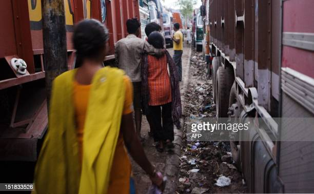 Indian truckers walk past parked trucks with female prostitutes at the Sanjay Gandhi Transport Nagar a transport rest area in New Delhi early on...