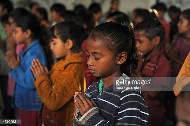 Indian underprivileged children pray before their lessons at Palodia village of Gandhinagar district some 25 kms from Ahmedabad on November 21 2013...