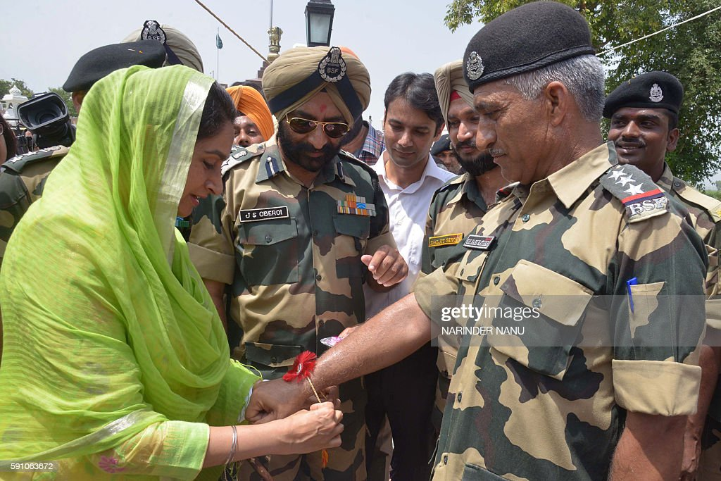 Indian Union Minister for Food Processing Industries Harsimrat Kaur Badal ties a `rakhi` or sacred thread onto the wrist of an Indian Border Security.
