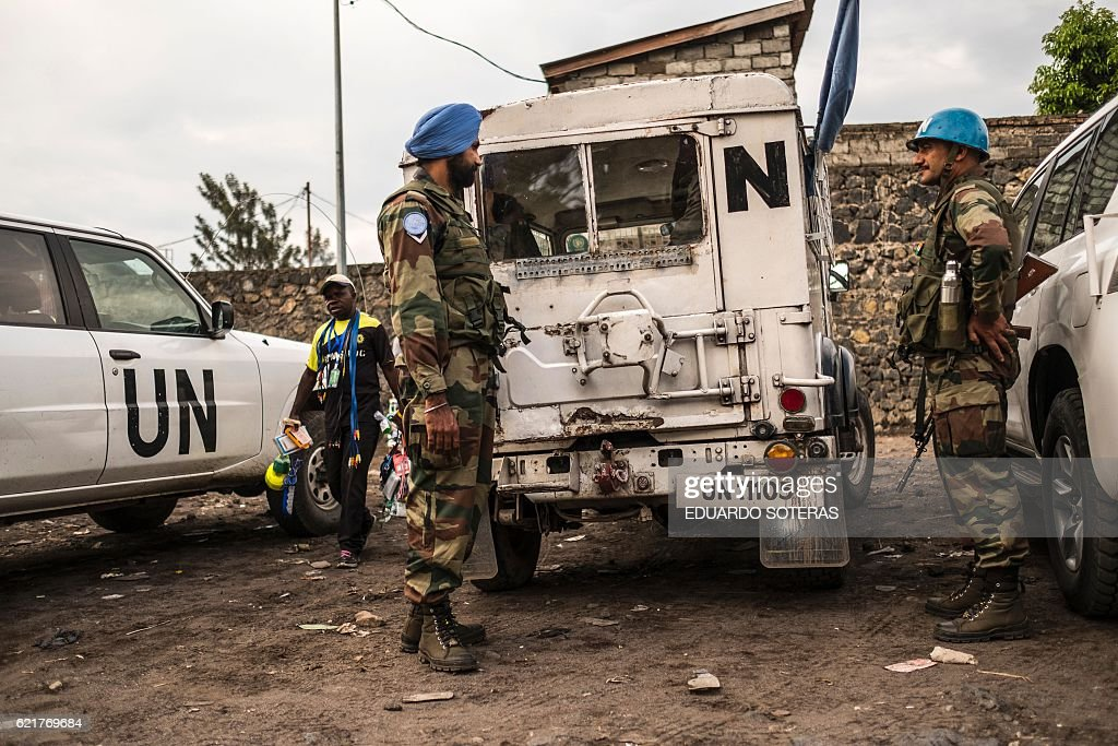 Indian United Nations Organisation Stabilisation Mission in the Democratic Republic of Congo (MONUSCO) Blue Helmet peacekeepers stand guard next to United Nations vehicles in Goma on November 8, 2016. An Improvised Explosive Device (IED) killed a Congolese schoolgirl, and wounded at least 31 Indian Blue Helmets peacekeepers and one Congolese Civilian, on early morning of November 8 in Goma. The blue helmets were struck as they were exercising and the injured servicemen were taken to a UN military hospital. / AFP / Eduardo Soteras