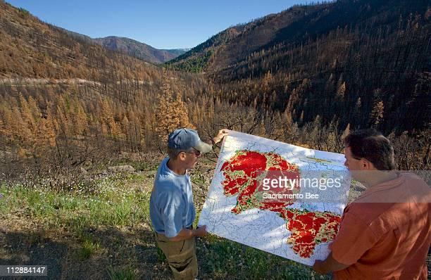 Indian Valley residents John Shower left and Jason Moghaddas hold a Plumas County map June 4 which shows the devastation of fire in red where the...