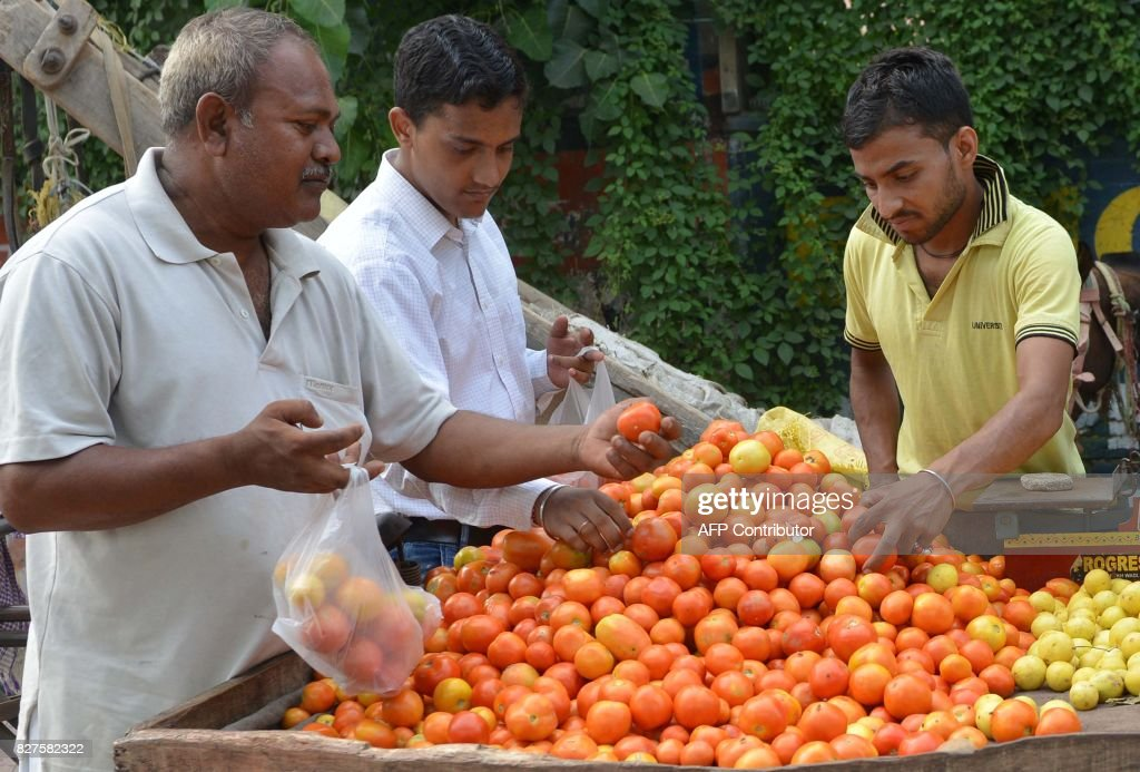 Indian vegetable vendor Niranjan sells tomatoes and lemonn to customers at a roadside stall in Amritsar on August 8 2017 / AFP PHOTO / NARINDER NANU