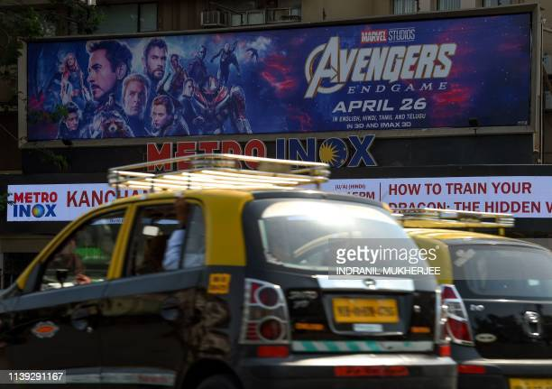 Indian vehicles go past a movie theatre displaying a poster of the latest Avengers movie in Mumbai on April 25 2019 Marvel's 'Avengers Endgame' the...